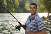 Portrait of man fishing on river and holding rod — Stock Photo