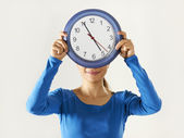 Happy asian girl holding big blue clock — Stock Photo