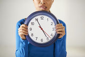 Asian girl holding big blue clock with stress — Stock Photo