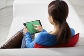 Asian girl using touch pad device — Stock Photo