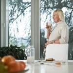Portrait of senior woman having breakfast with milk — Stock Photo