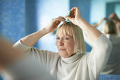 Senior woman checking hairline for hair loss — Stock Photo