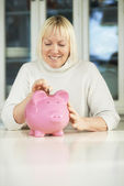 Old woman showing piggybank and euro coin — Stock Photo