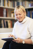 Senior woman using touch pad device — Stock Photo
