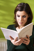 Girl studying literature with book at home — Stock Photo