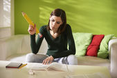 Female student doing homeworks with big pencil — Stock Photo