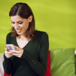Portrait of girl reading sms on smarthphone at home — Stock Photo