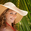 Portrait of woman with straw hat at beach smiling — Stock Photo