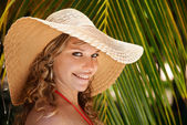 Portrait of woman with straw hat at beach smiling — Stok fotoğraf