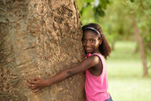 Portrait of black ecologist girl hugging tree and smiling — Stock Photo