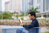 Portrait of asian office worker with ipad on bench — Stock Photo