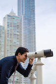 Asian business man with binoculars looking at city — Stock Photo