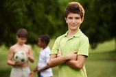Portrait of boy and friends playing football in park  — Stok fotoğraf