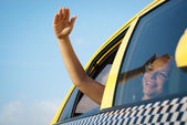 Woman in taxi waving hand out of car window — Stock Photo