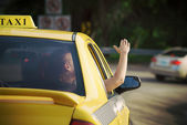 Женщина в такси, махнув рукой из окна автомобиля — Стоковое фото