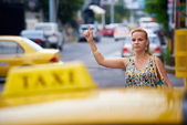 People travelling-business woman stopping yellow taxi — Stock Photo
