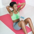 African woman doing series of crunch in gym — Stock Photo #9305642