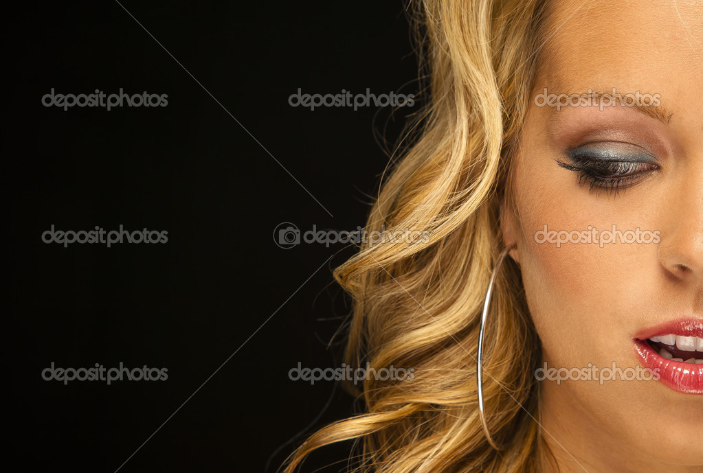 Parcel view of a blonde female model in a studio environment against a black background  Stock Photo #12434650