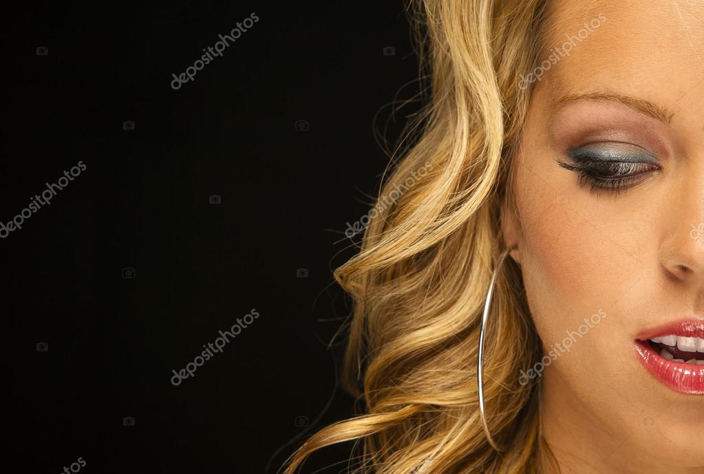 Parcel view of a blonde female model in a studio environment against a black background   #12434650
