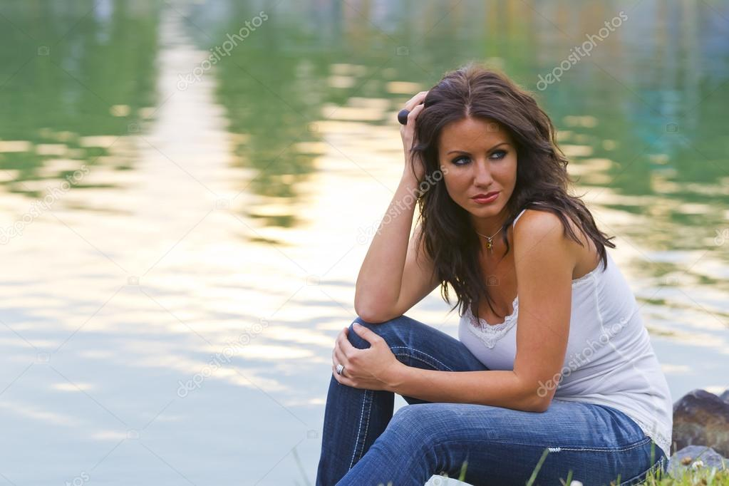 Brunette model sitting in a park near a pond — Stock Photo #12564670