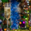Champagne is poured into a glass against the lights of the Chris - Stock Photo