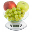 Peaches, apples and grapes in the balance — Stock Photo
