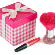 Lip gloss, a brush for powder and gift wrap — Stock Photo