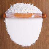 Holz nudelholz mit weißen weizenmehl auf dem tisch. ansicht von oben — Stockfoto