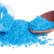 Blue bath salt in a glass jar and a wooden spoon isolated - Stock Photo