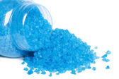 Blue bath salt spilled out of a glass jar isolated on white — Stock Photo