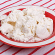 Cottage cheese in a red plate against a striped tablecloth — Stock Photo