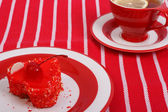 Fresh gelled cake on a plate and red tea on striped tablecloth — Stock Photo