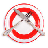 Crossed fork and knife on a plate with a red border — Stock Photo