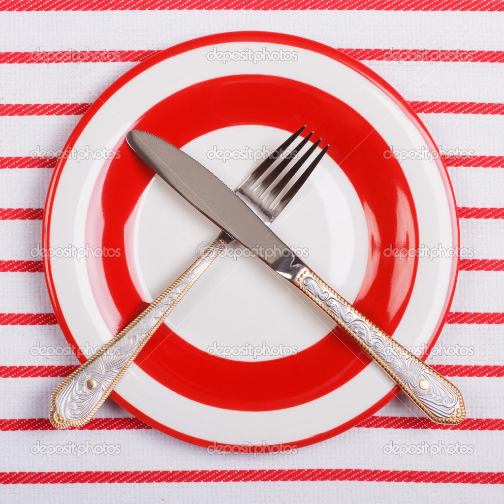Cuchillo cruzado y tenedor en un plato rojo sobre mantel for Plato tenedor y cuchillo