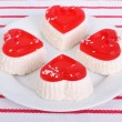 Cakes in the shape of a heart with coconut on a white plate - Stock Photo