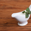 White sauce with mint leaves in a gravy boat on a wooden table — Stock Photo #23886685