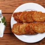 Potato pancakes with sour cream sauce top view — Stock Photo #23886689