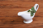 White sauce with mint leaves in a gravy boat on a wooden table — Stock Photo