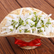 Snowdrop flowers in a basket with red bow close-up - Stock Photo