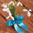 Bouquet of snowdrops tied a blue ribbon on a wooden table - Stock Photo