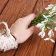 Stock Photo: Snowdrops in a female hand with a bracelet on a birch