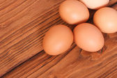 Fresh brown chicken eggs on an oak wood table — Stock Photo