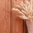 Wheat ears in a vase on a wooden boards background — Stock Photo