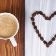 Coffee and heart from coffee beans on wooden surface — Stock Photo #24744087