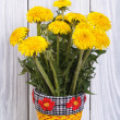 Dandelion flowers in a yellow vase on a wooden boards background - Stock Photo