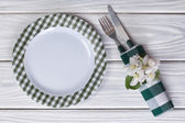 Plate and cutlery decorated with flowers of apple on a wooden table. Top view. — Stock Photo