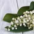 Lilies of the valley on the gray wooden plank close-up — Stock Photo