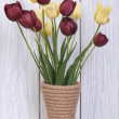 Bouquet of different color tulips in a vase on a wooden — ストック写真