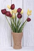 Ramo de tulipanes de diferentes colores en un florero de madera — Foto de Stock