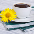A cup of coffee and chamomile on a wooden table with a napkin — Stock Photo
